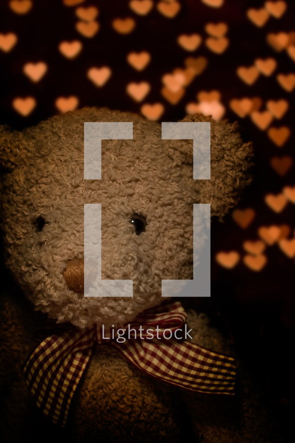 teddy bear in front of heart lights