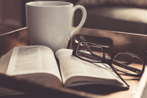 Coffee cup, reading glasses, open Bible