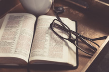 Coffee cup, reading glasses, and an open Bible