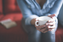 a woman holding a cup of coffee praying