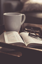 Tea cup, Bible, and reading glasses on a tray