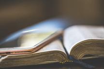 a cellphone on an open Bible