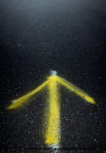 spray painted arrow on asphalt