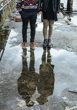 a couple standing near a puddle holding hands