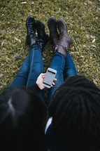 friends sitting in the grass looking at a cellphone