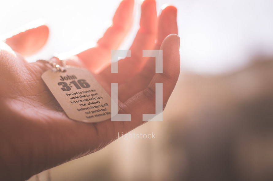 A hand holding a dog tag with John 3:16.
