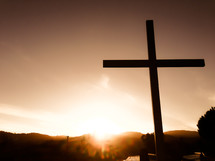 cross and a setting sun