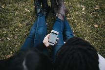 friends sitting in the grass looking at a cellphone screen