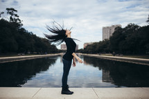 a woman flipping her hair standing by a pond in a city