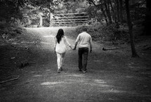 man and woman holding hands walking country lane