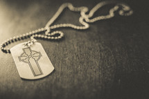 A dog tag with a cross on it.