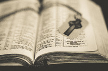 A cross dog tag on the pages of a Bible.