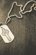 A cross dog tag necklace.