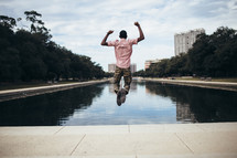 an African-American man leaping in the air near a pond in a city