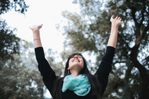 a woman standing outdoors with raised hands