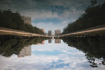a reflection in the water of a pond in a city
