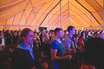 congregation under a tent signing