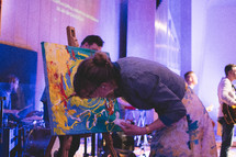 a woman painting during a worship service