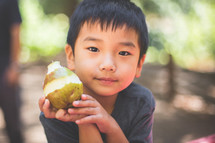 a boy child eating a pear
