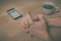praying hands by a cellphone opened to an app for online giving