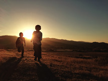 Silhouette of young boys running through the grass by the mountains at sunset.