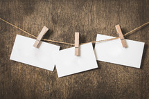 blank note cards hanging on a line with clothespins