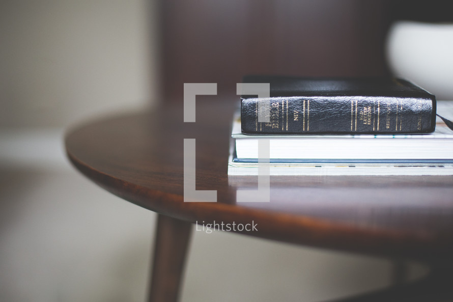 Bible and books on an end table
