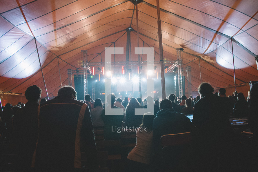 crowds of people under a tent at a concert
