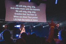 lyrics on a projection screen at a worship service