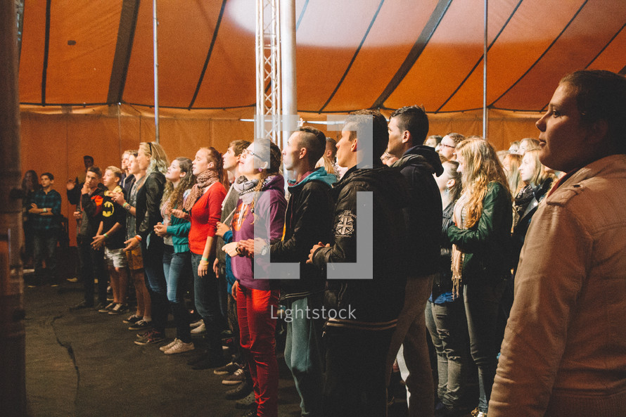 people standing and singing under a tent