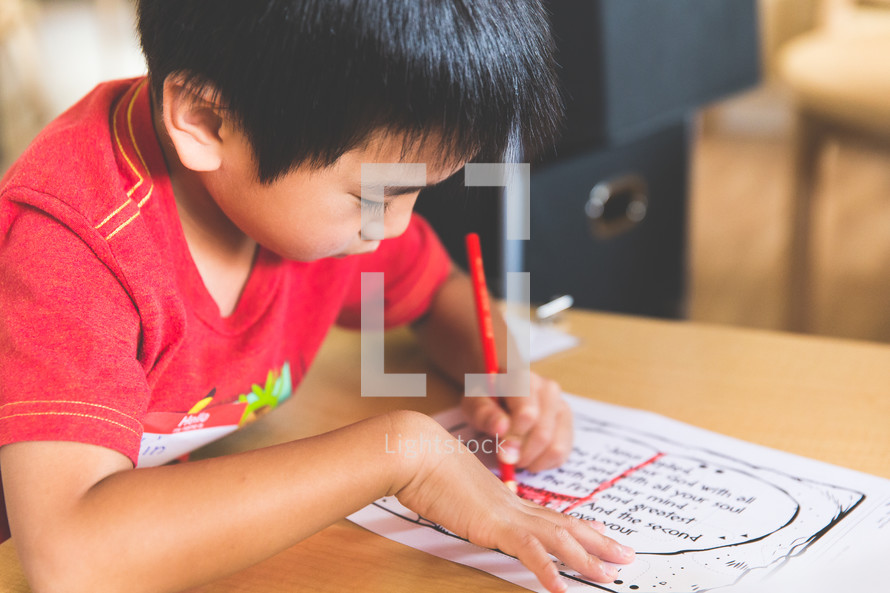 a boy child coloring with crayons