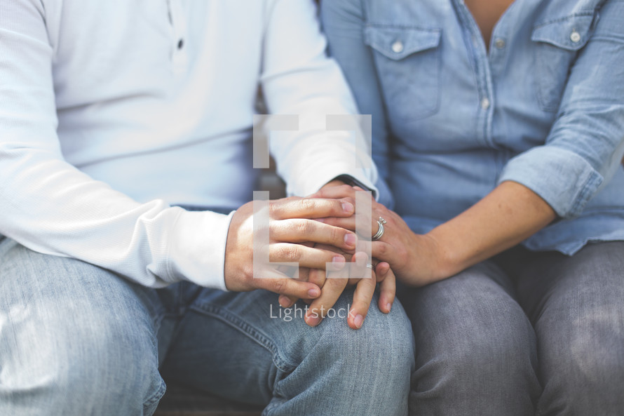 a couple holding hands in prayer