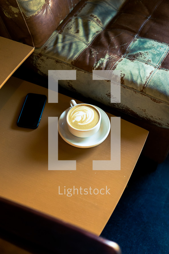 a latte on an end table next to a couch