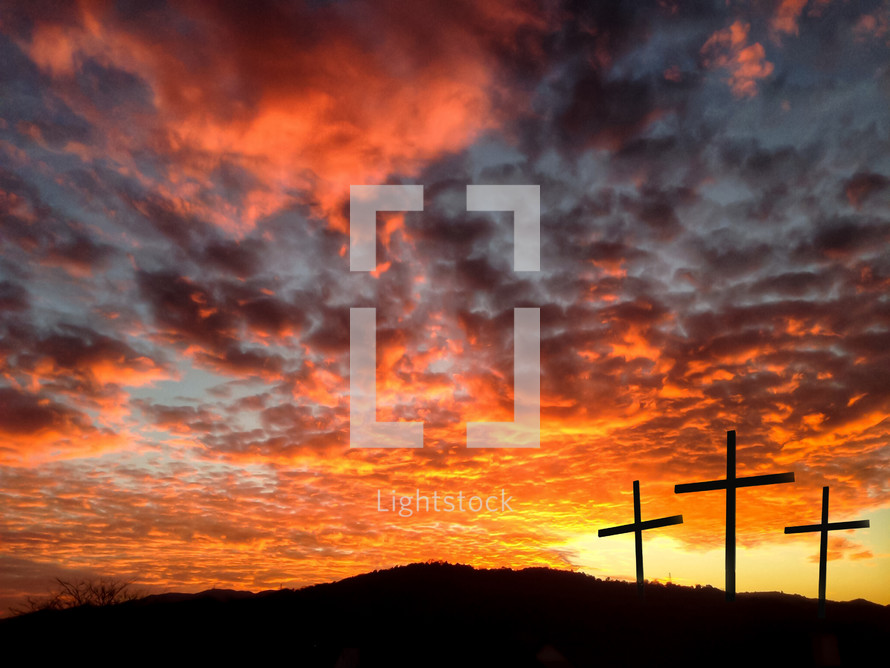 silhouette of three crosses against a fiery sky