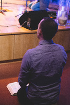 a man kneeling before a stage with a Bible