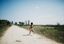 a boy child running down a dirt road