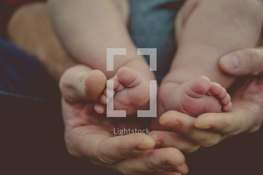 Infant's feet in a parent's hands.