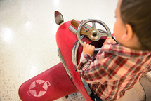 A child sitting in a weathered pedal red airplane.