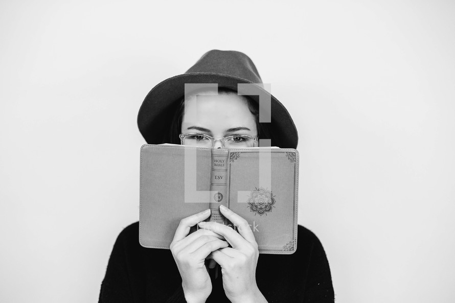 a woman peeking over a Bible