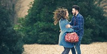 a happy young couple bouncing around outdoors