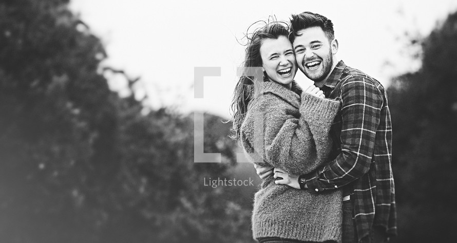 A man and woman laughing and embracing.