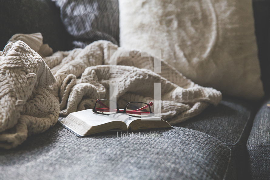 blanket, reading glasses, and Bible on a couch