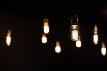 hanging glowing lightbulbs against darkness