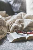 reading glasses, blanket, cellphone, earbuds, and open Bible on a couch