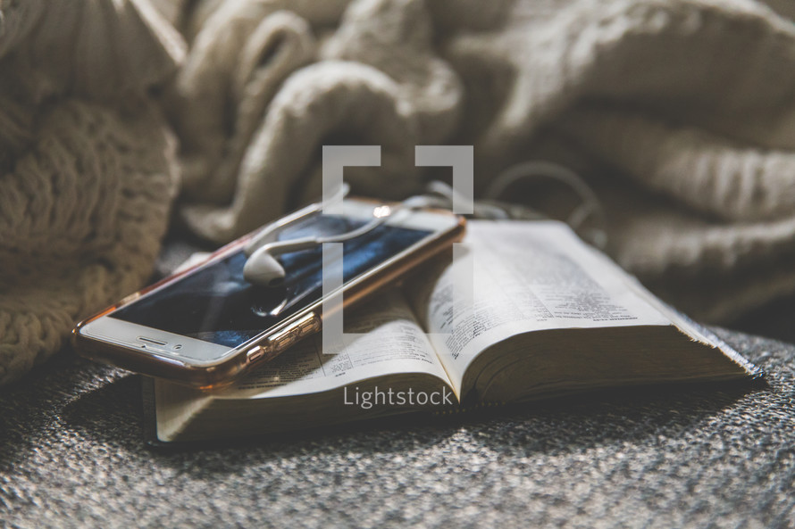 blanket, cellphone, earbuds, and open Bible on a couch
