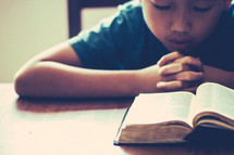child praying in front of a Bible