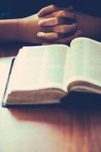 man praying in front of a Bible