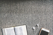 cellphone, earbuds, and open Bible on a couch
