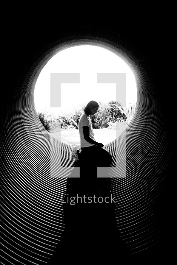 woman in prayer in a tunnel
