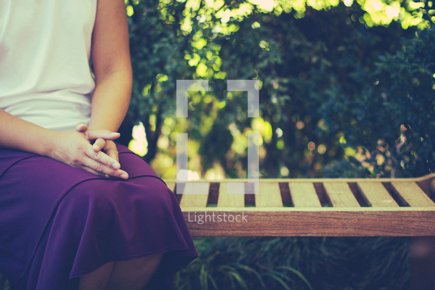 woman sitting on a bench in prayer